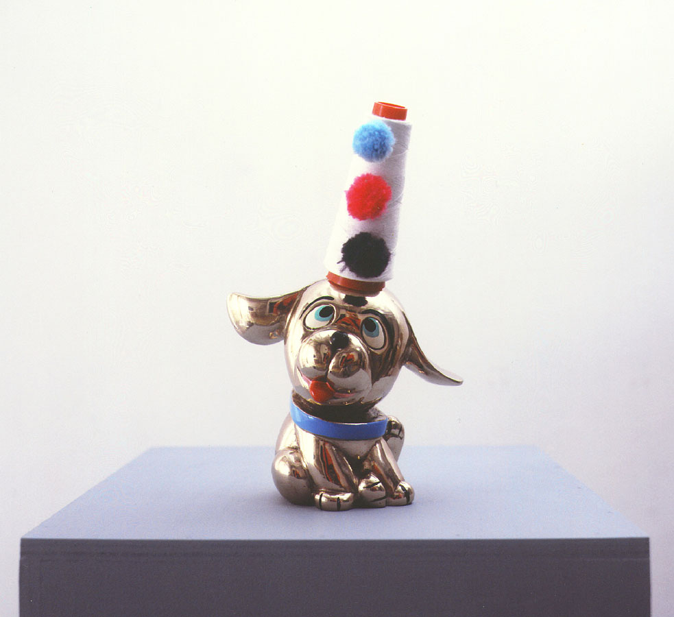 Perrito Payaso, 2001. De la serie Trabajos manuales artísticos. Bronde pintado y cono de hilo con pompones de lana